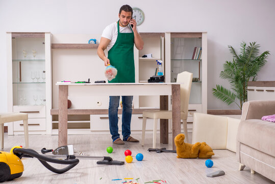 Young male contractor cleaning the flat after kids' party