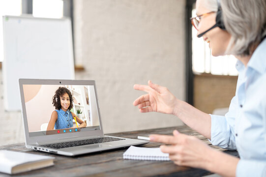 Mature gray-haired businesswoman in headset having virtual meeting with the client, online business video call via laptop from home office. Senior woman looking at the screen and talking to young lady