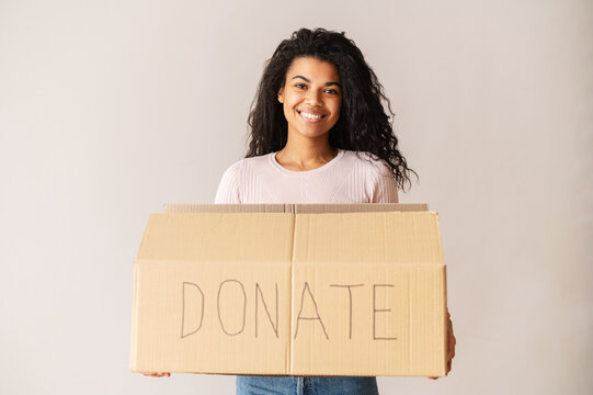 Kind smiling African American female volunteer with curly dark hair holding a cardboard box, donating her things to charity, for orphans and homeless, for reuse or recycle of clothes or toys