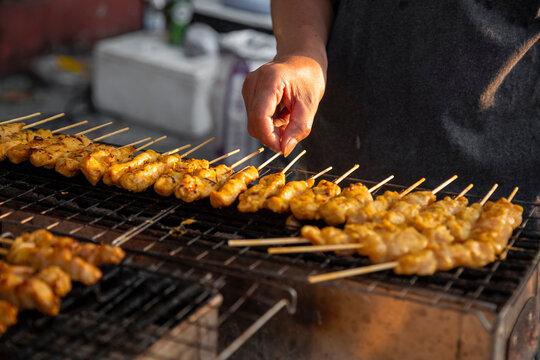 Meat skewers cook over hot coals in Satay Street food market