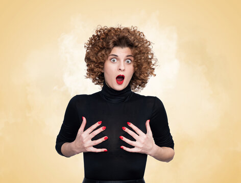 Young pretty woman with a surprised expression on her face grabbing her chest with her hands. On yellow and smoke background