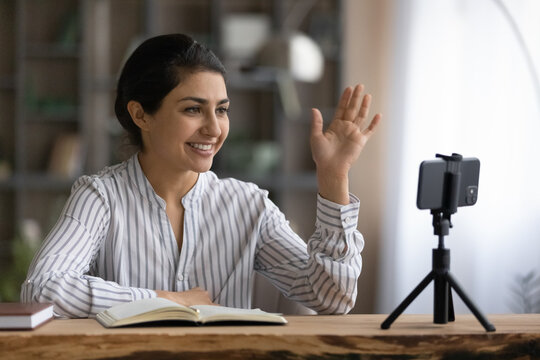 Happy Indian female teacher or tutor wave greet talking on video call on smartphone. Smiling young ethnic woman have webcam digital online lesson or webinar on cellphone. Virtual event concept.
