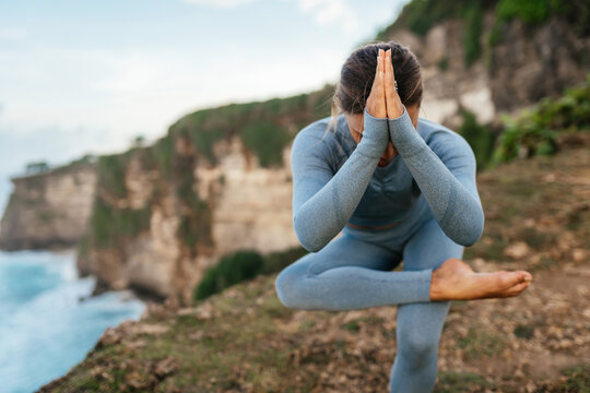 Beautiful woman doing yoga on a cliff, behind an amazing view in the ocean Bali Indonesia