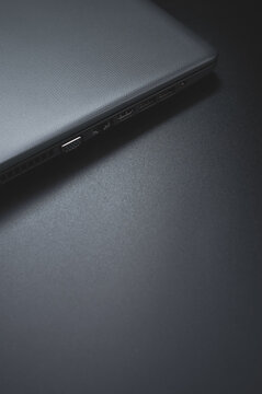 Vertical closeup shot of the laptop ports on the grays background