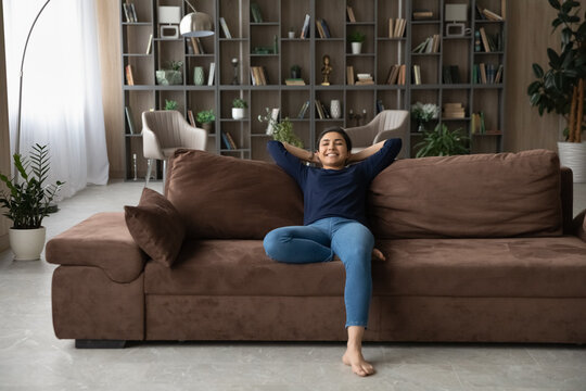 Happy young Indian female renter or tenant sit relax on comfortable couch in modern living room. Smiling millennial ethnic woman rest on sofa at home, nap or sleep dreaming. Stress free concept.