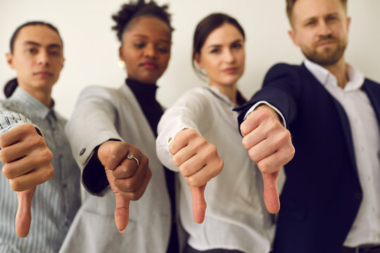Group of young diverse people giving thumbs down, hands in closeup. Multiracial corporate HR managers saying no and refusing a person. Multiethnic business team showing dislike of bad work