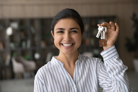 Headshot portrait of smiling young Indian woman hold show keys to new home or apartment. Profile picture of happy ethnic female renter or tenant celebrate moving relocation to own house. Rent concept.