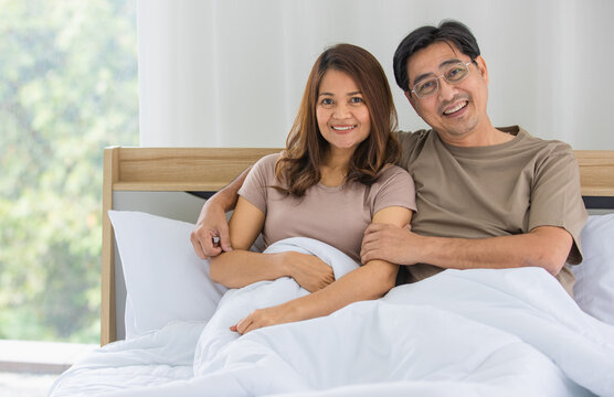closeup of a happy middle age Asian husband and wife sitting on a bed together while a man put his arm around the shoulder of a woman smiling at a camera