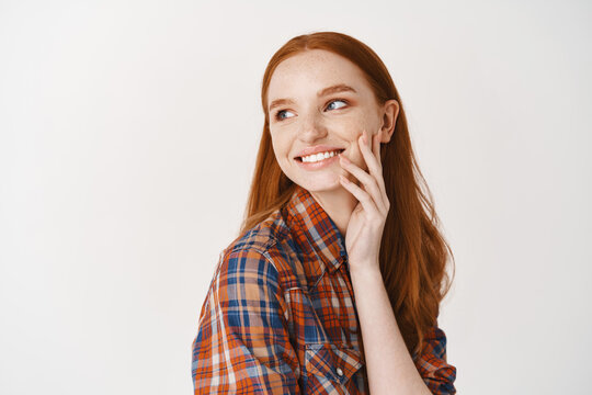 Beautiful coquettish redhead girl smiling with white perfect teeth, touching pale face without makeup and looking left happy, standing over white background