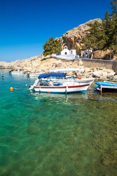 charming bay with blue sea and small orthodox chapel in Lindos on Rhodes island in Greece