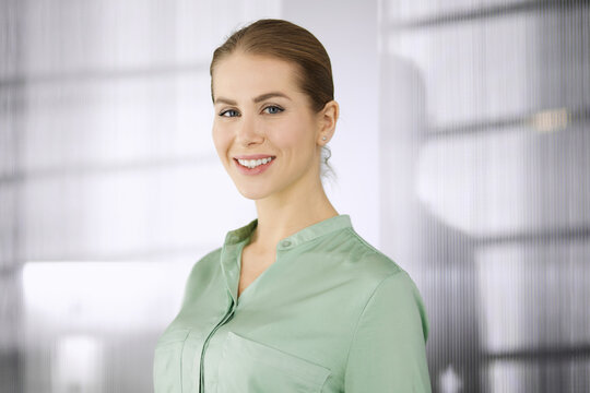 Beautiful adult business woman dressed in green blouse standing straight in office. Business headshot or portrait