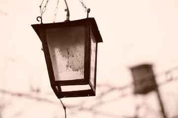 Old retro lantern hanging on a chain in the garden. Sepia photo. Fotobehang
