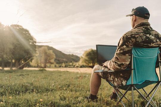 men using laptop outdoors at sunset