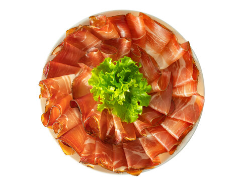 Plate of prosciutto speck ham with a salad leaf, plate of sliced smoked ham top view isolated on white background