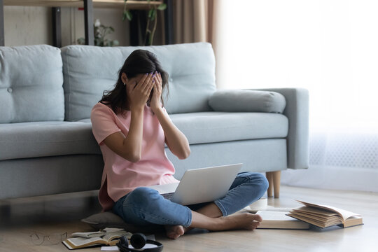 Depressed arabic lady remote worker sit on floor with laptop among books hide face in palms miss deadline burned out on work. Crying indian female student can not understand material lose motivation