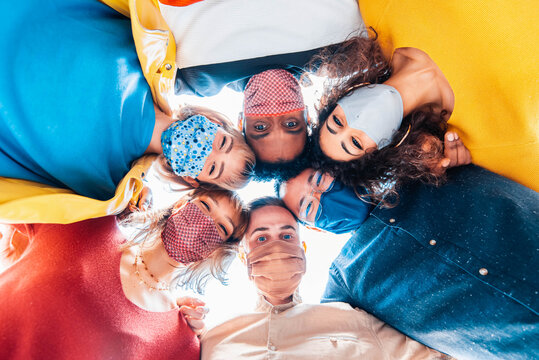 Multiracial group of friends wearing protective face masks taking a selfie - New normal friendship concept with young people looking down at camera and laughing - Bright filter