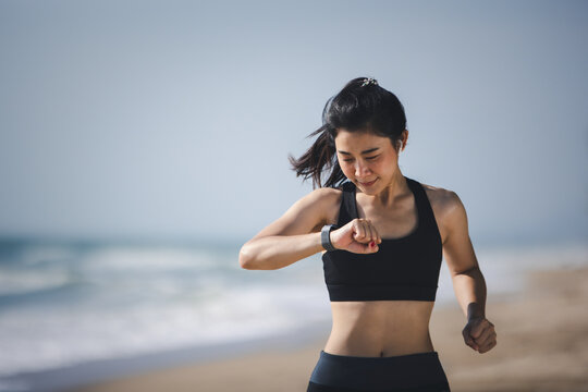 Well being sport concept, Asian muscular healthy woman jogging running looking at smart watch on beach