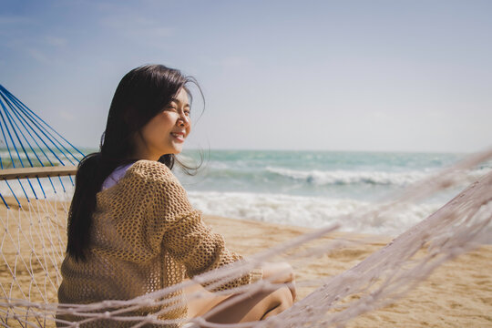 Summer vacation concept, Cheerful asian female tourist smiling relaxing sitting on hammock at beautiful beach