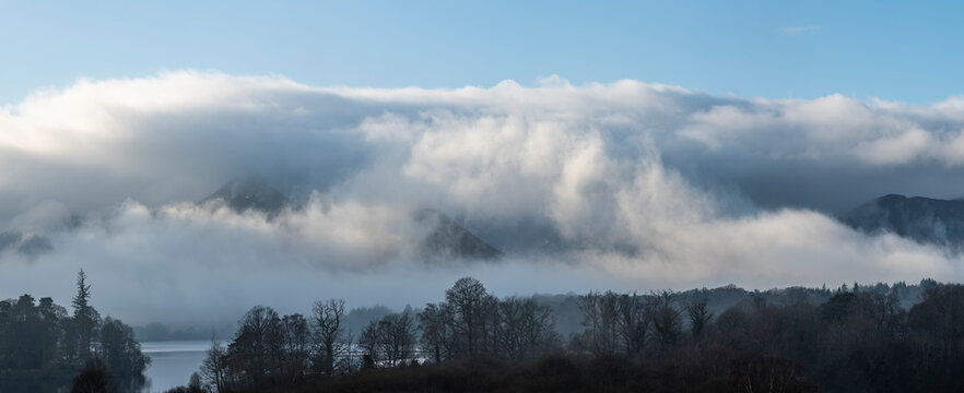 Dramatic landscape image looking across Derwentwater in Lake District towards Catbells snowcapped mountain with thick fog rolling through valley