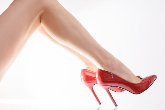 Skinny bare legs with red high-heeled shoes