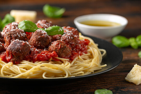 Vegetarian spaghetti with meat free, vegan meatballs in rich tomato sauce, grated cheese and basil leaves