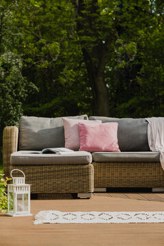 Pastel pink pillows on grey sofa in green garden with wooden terrace