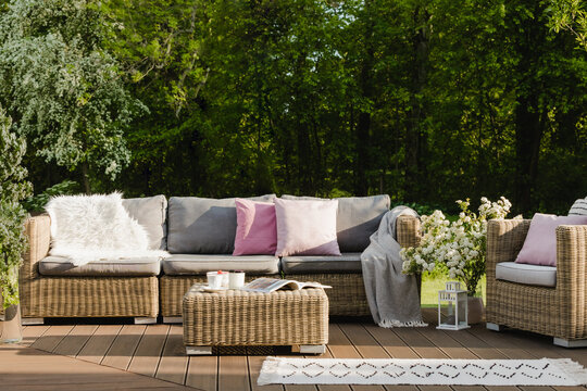 Cozy wooden terrace with grey sofa with pastel pink pillows and blanket