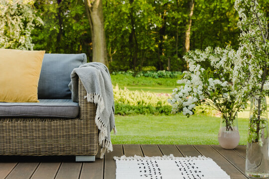 White flowers in vase next to wicker armchair on wooden terrace in green garden