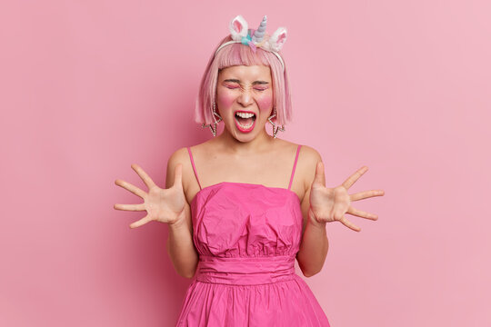 Emotional pink haired Asian woman with makeup and rhinestones on face raises palms screams angrily being irritated with something wears stylish dress unicorn headband isolated over rosy background