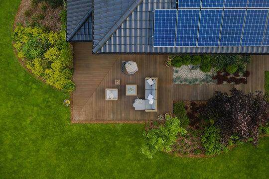 Top view of suburban house with green garden and wooden terrace