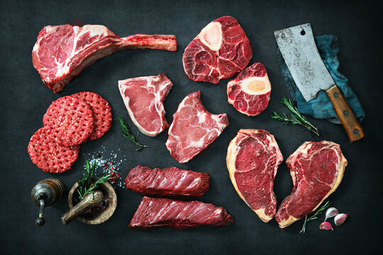 Variety of raw cuts of meat, dry aged beef steaks and hamburger patties