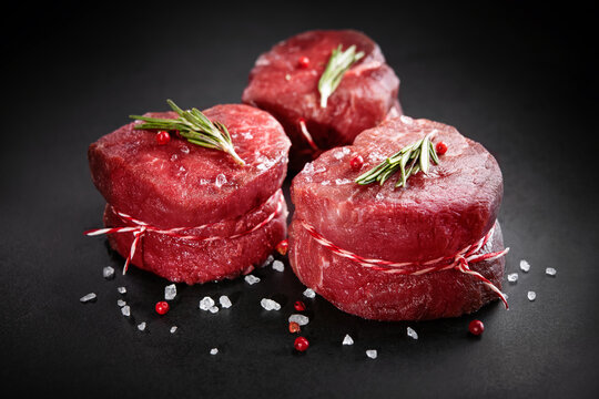 Raw beef filet mignon steaks with rosemary, pepper and salt on dark rustic board