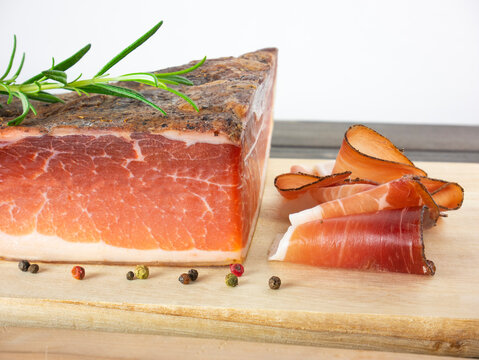 Speck ham cut into soft slices on a wooden cutting board, prosciutto South Tyrolean cured meat with peppercorns
