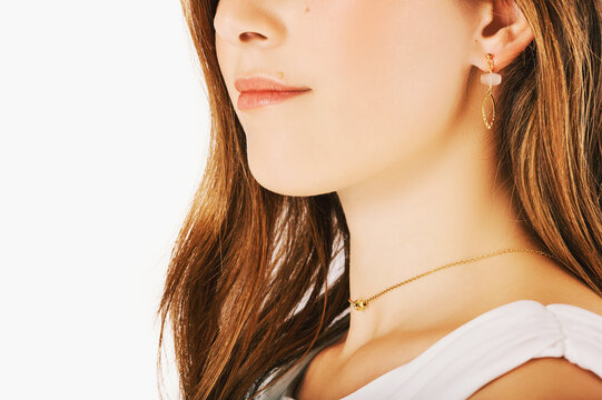 Close up image of beautiful woman wearing stylish earrings and tiyn necklace