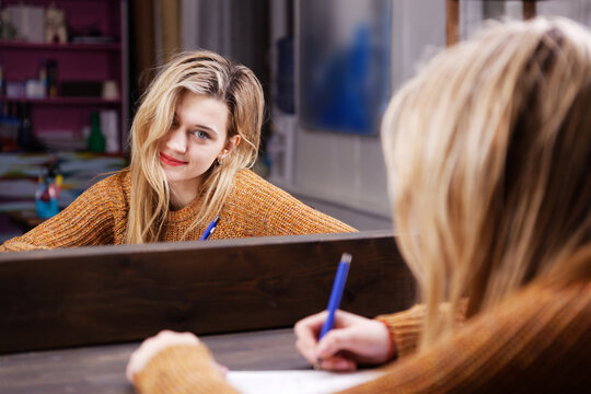 Young woman sits at a table in front of a mirror and writes something with a pen in a notebook. Shallow focus.