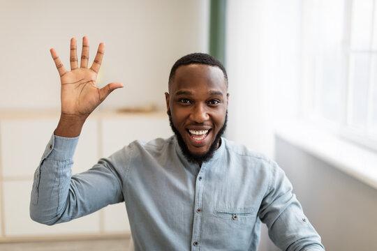 Joyful Black Businessman Waving Hand Posing Sitting At Workplace Indoors