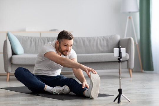 Cheerful sporty man stretching on fitness mat, broadcasting with smartphone