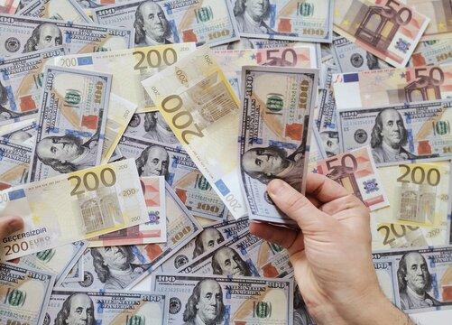 Background dollar and euro.Hand holding money.  Hand holding one hundred dollars and two hundred euros.