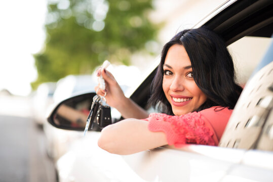 woman driving car looks out the window and shows keys to camera
