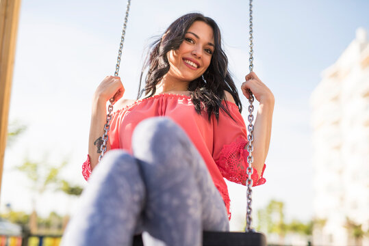 lonely young woman has fun on a swing outside a park