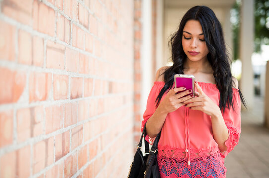 woman walks down the street looking at the mobile near a brick wall