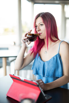 Pink haired woman drinking coke in bar, looking tablet