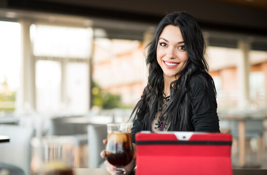 Pretty dark haired woman looking tablet in bar