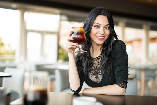 Pretty dark haired woman lookingat camera and drinking coke