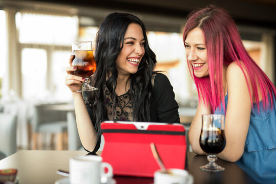 two pretty women looking tablet in bar while drinking coke and coffee