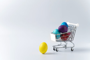 Yellow egg and multi-colored painted Easter eggs in a food cart on a light background. Copying...