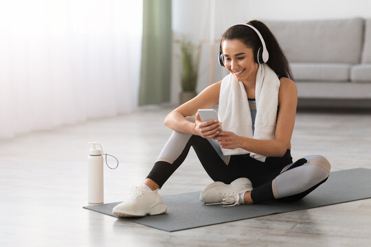 Happy young woman resting on yoga mat, listening to music