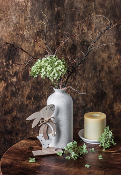 Easter still life - vase with dried hydrangea flowers, candle and  wooden figure of an easter bunny on a wooden table