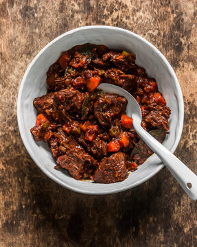 Slow cooker beer beef stew on a wooden background, top view. Delicious comfort homemade food