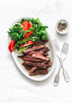 Beef steak and kale, tomato salad - delicious balanced diet lunch on a light background, top view